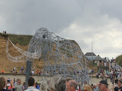 The articulated model of the West Runton Elephant walking along the beach in 2014