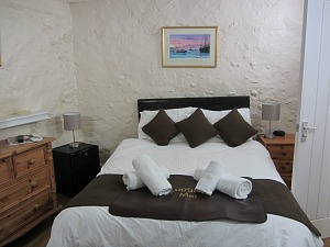 The small double room in The Stables at The Lobster with original 1840s stone wall