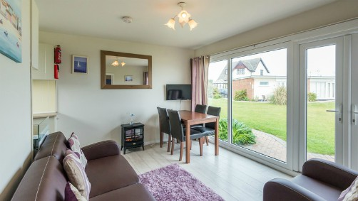 The sitting room/diner in one of the Hickling Chalets